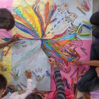 Séance de groupe filles-garçons. Réalisation d'un mandala mains pour rassembler les différences de chacun. Travail réalisé au sol sur un support commun construit ensemble.